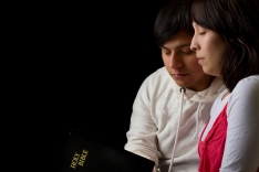 Hispanic Couple Studying the Bible and Praying in the Dark